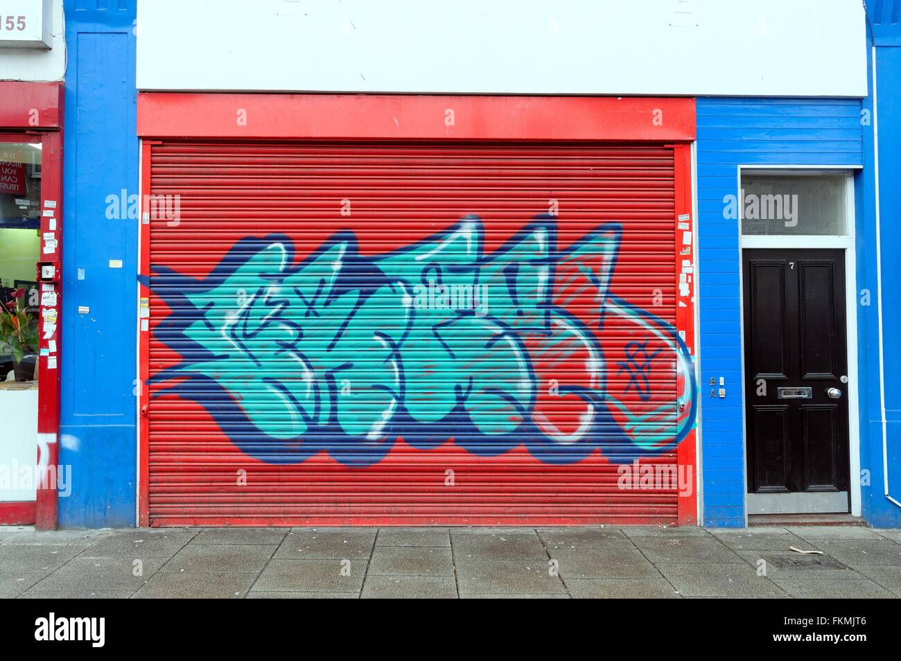 Graffiti on shuttering of a closed shop in London - Stock Image