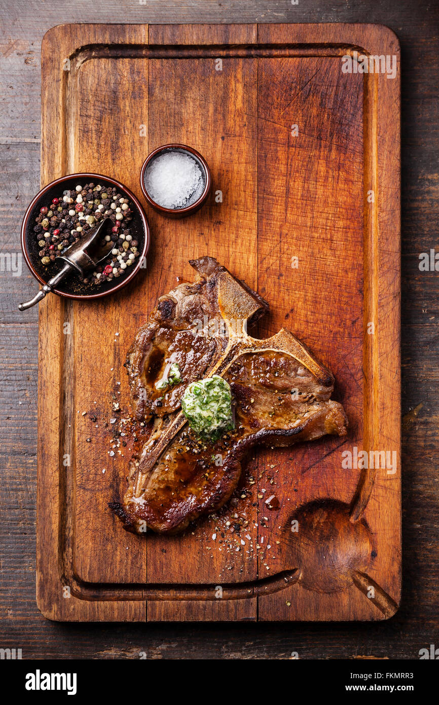 Grilled T-Bone Steak and herb butter on wooden cutting board - Stock Image