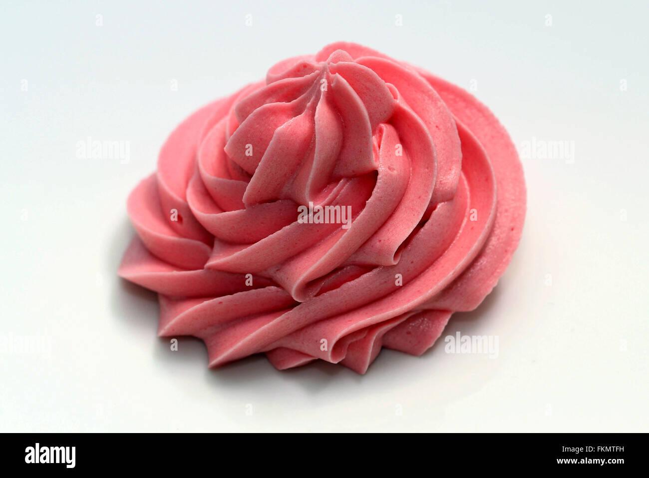 swirl pink icing cream on white background - Stock Image