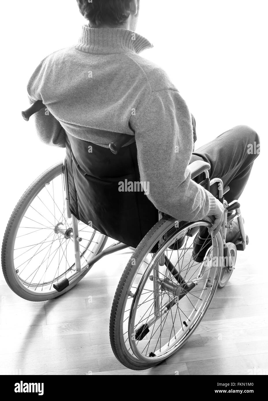 disabled elderly sitting in a wheelchair in the room in front of the window - Stock Image