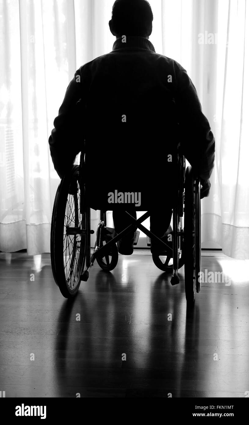 disabled elderly sitting in a wheelchair - Stock Image