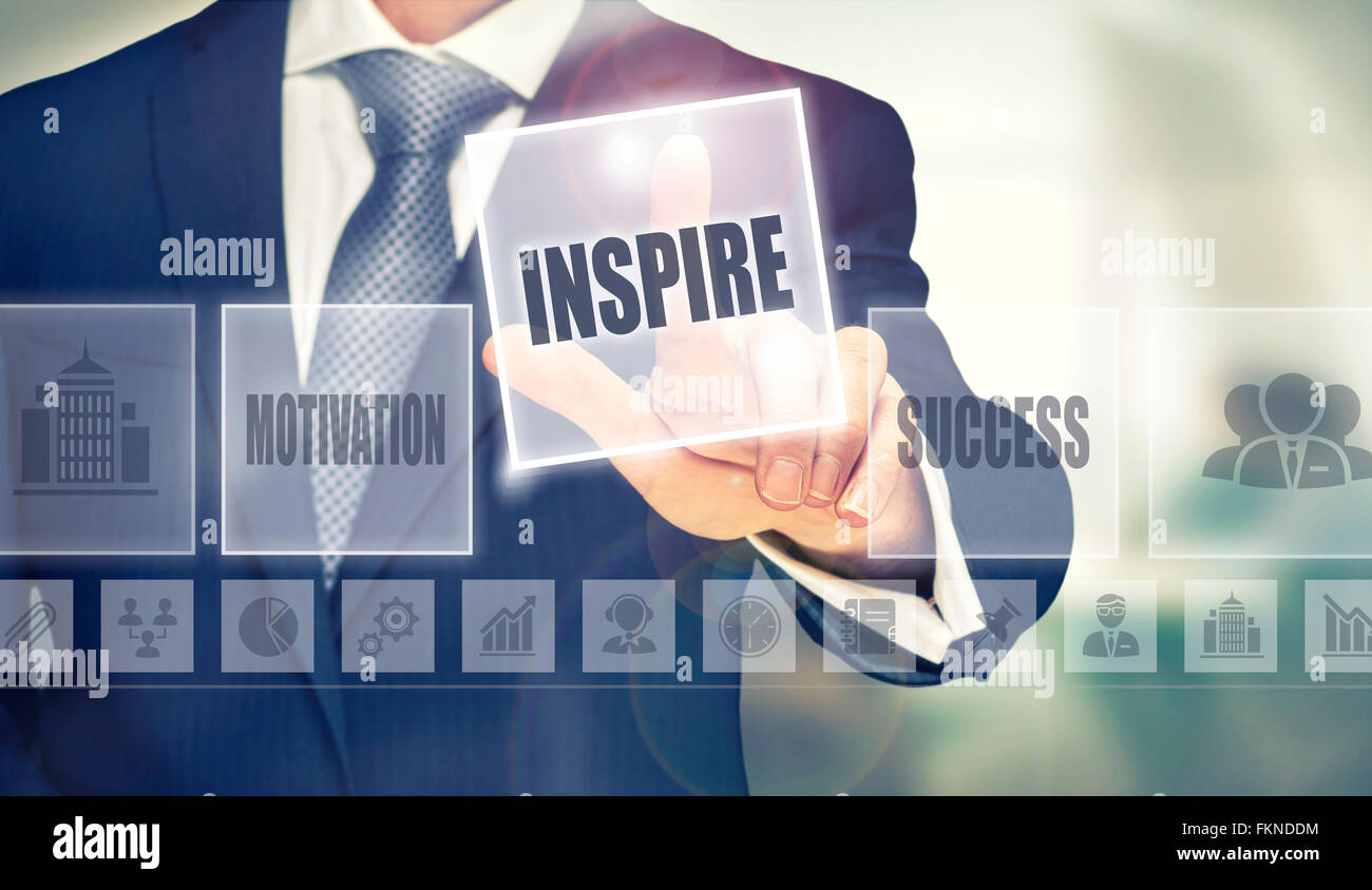 Businessman pressing an Inspire concept button. - Stock Image