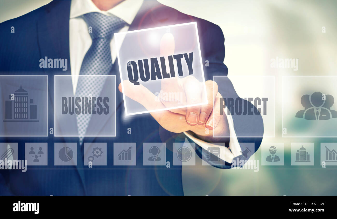 Businessman pressing a Quality concept button. - Stock Image