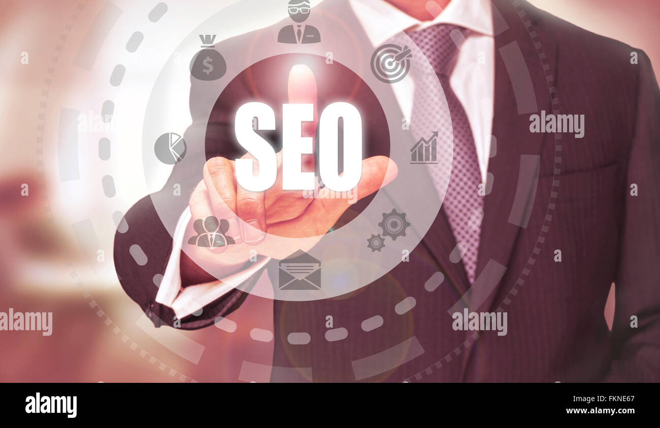 Businessman pressing an SEO concept button. - Stock Image