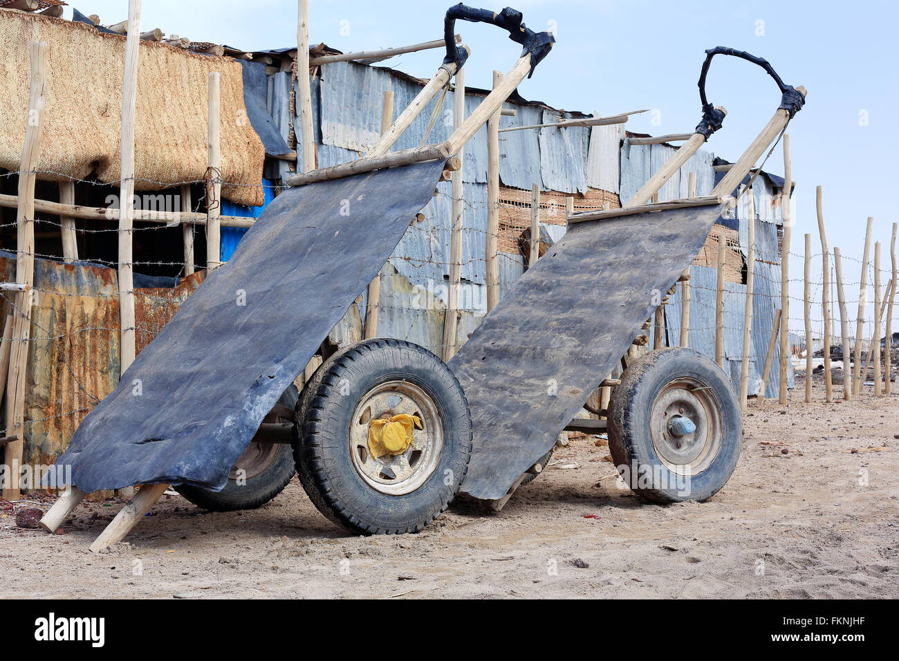 Two wheeled wooden carts-tin platforms for transportation of salt stationed beside the barbed wire fence of tin - Stock Image