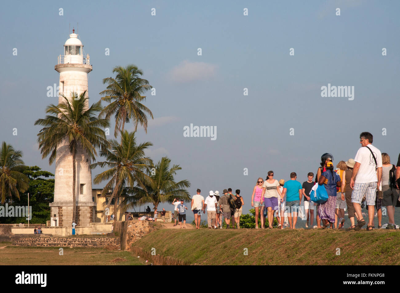 Tourists join local residents in the evening promenade along the ramparts of Galle Fort, Sri Lanka - Stock Image