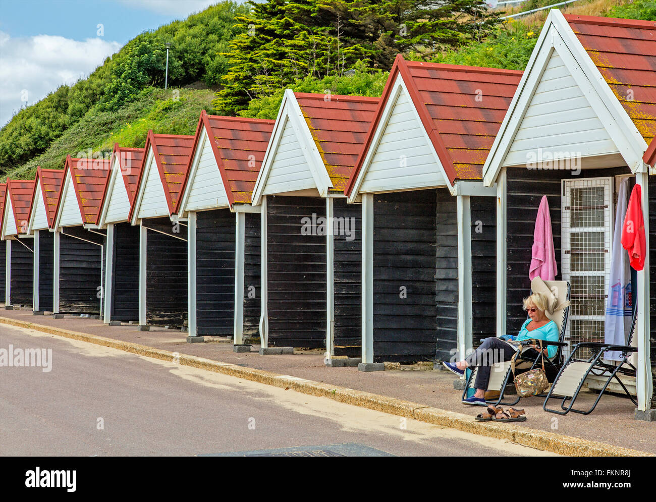 Lady relaxes in the sun, outside her beach hut, at Brighton beach / promenade, UK - Stock Image