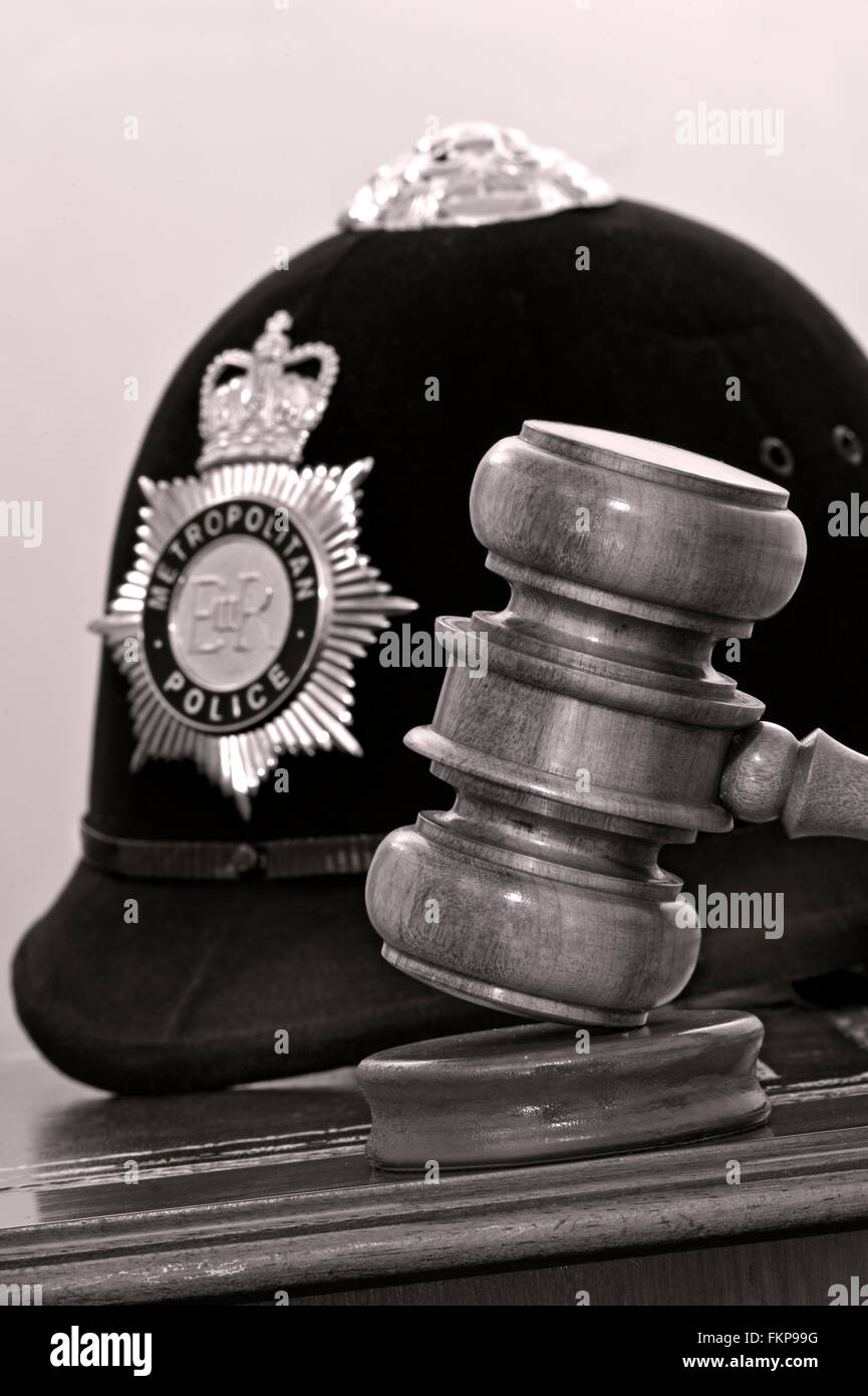 Legal concept Metropolitan Police helmet with judges gavel in London law courts situation UK (B&W toned) - Stock Image