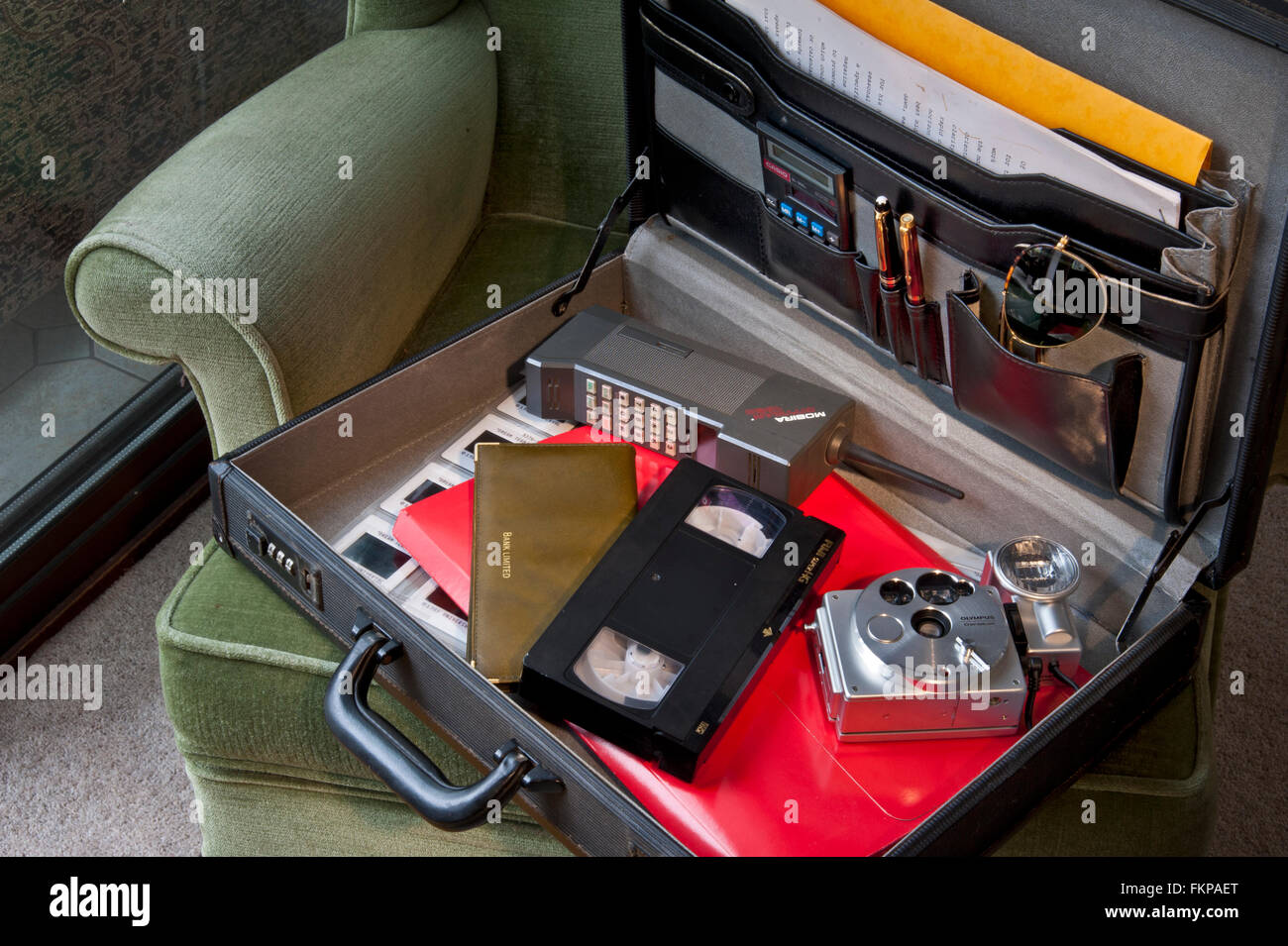 Briefcase with typical 1980's items including Mobira Cityman mobile phone, VHS video cassette, 35mm film camera, - Stock Image