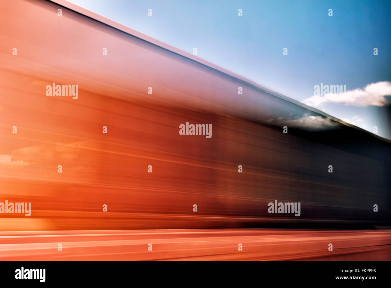 Abstract of train car passing by with pseudo double exposure of sky produced by slow exposure - Stock Image