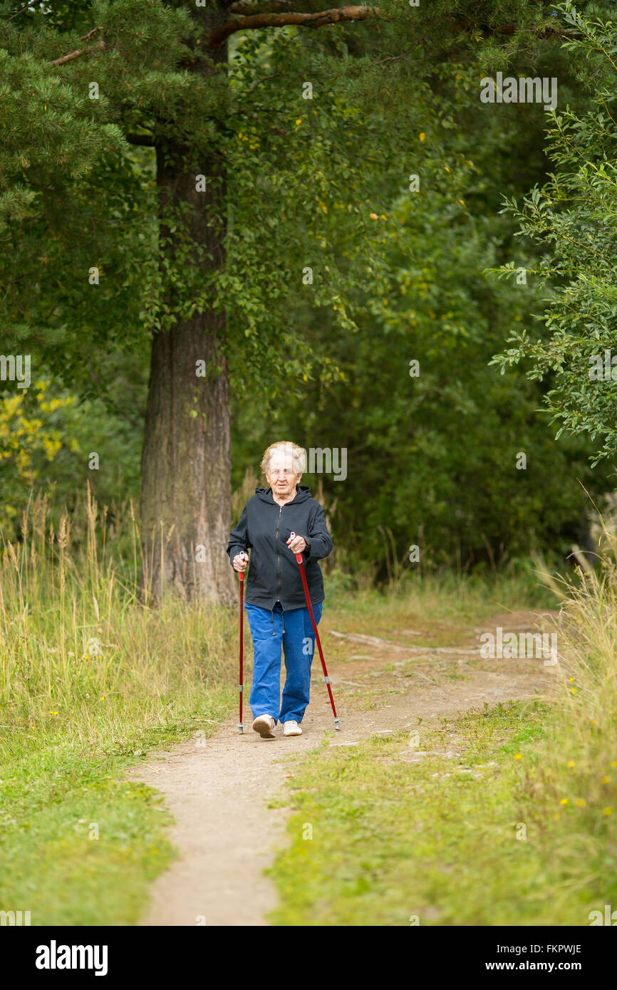 An elderly woman is engaged in Nordic walking in the nature. - Stock Image