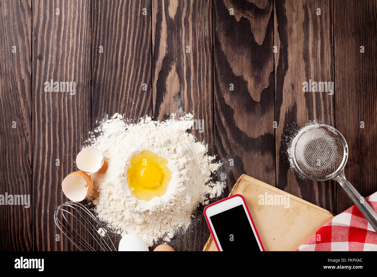 Kitchen table with ingredients, utensils and vintage recipe cooking book. Top view with copy space - Stock Image