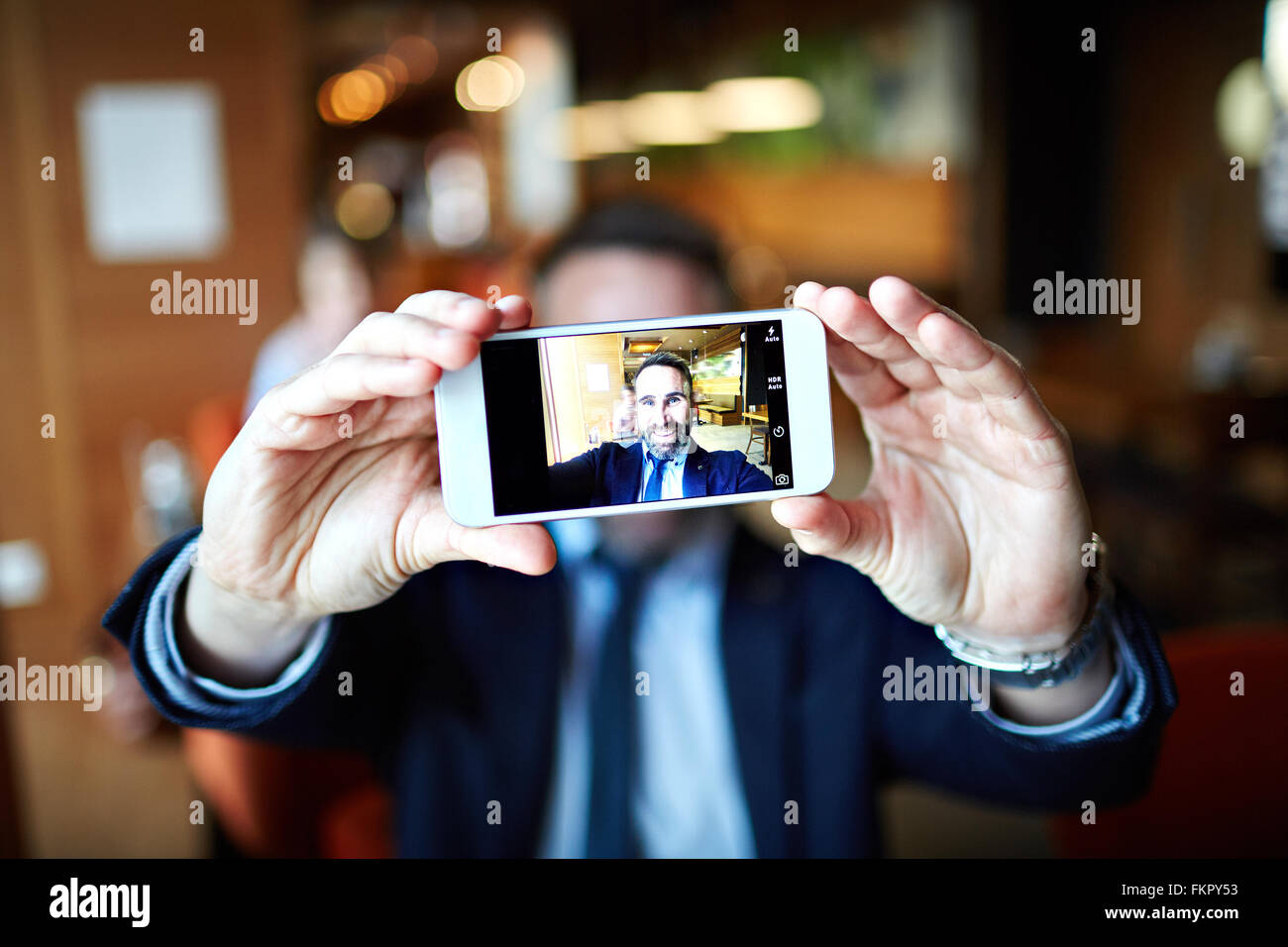 Smiling businessman taking selfie with his cellphone Stock Photo