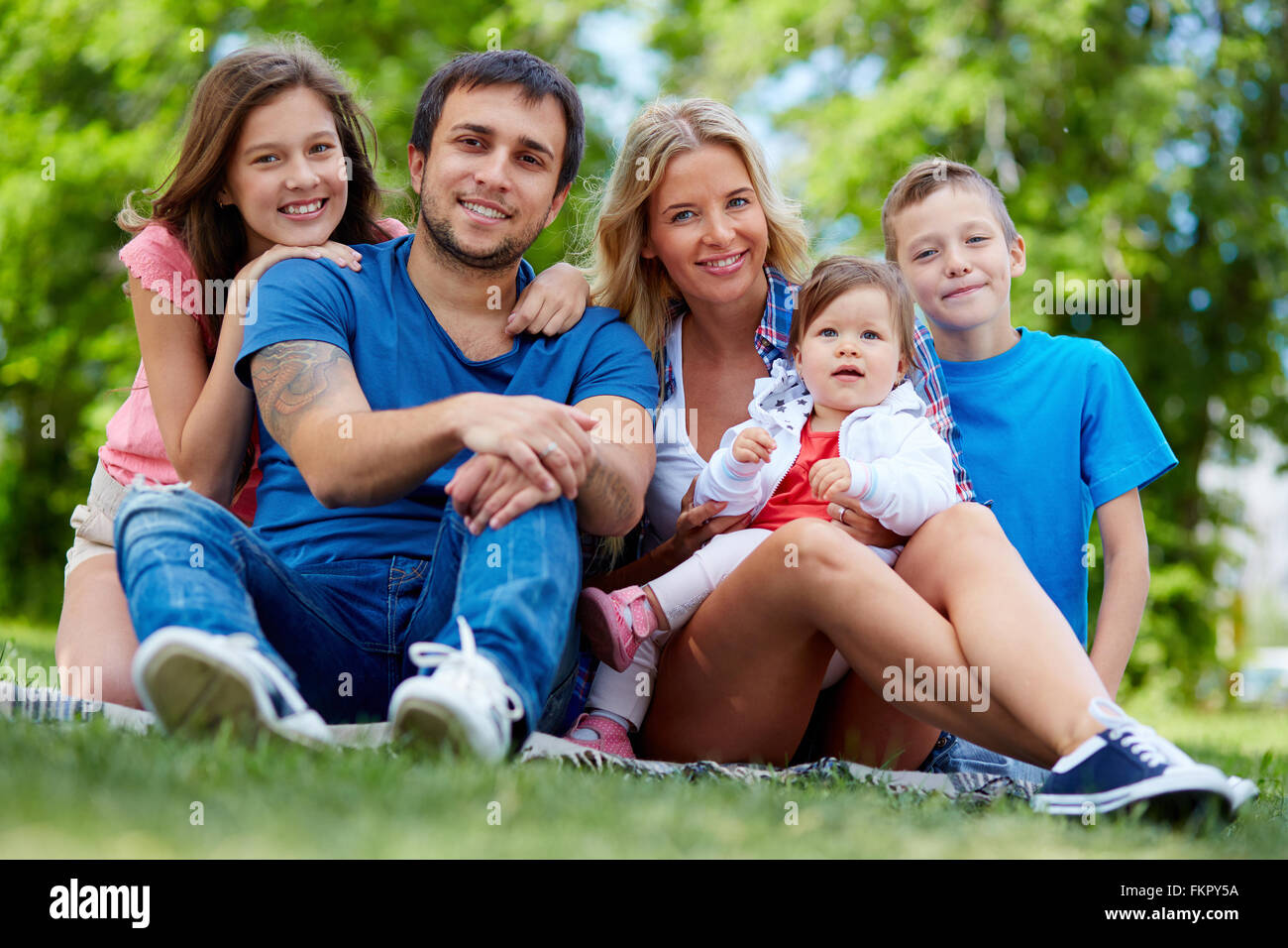 Portrait of a happy family of five sitting on grass - Stock Image