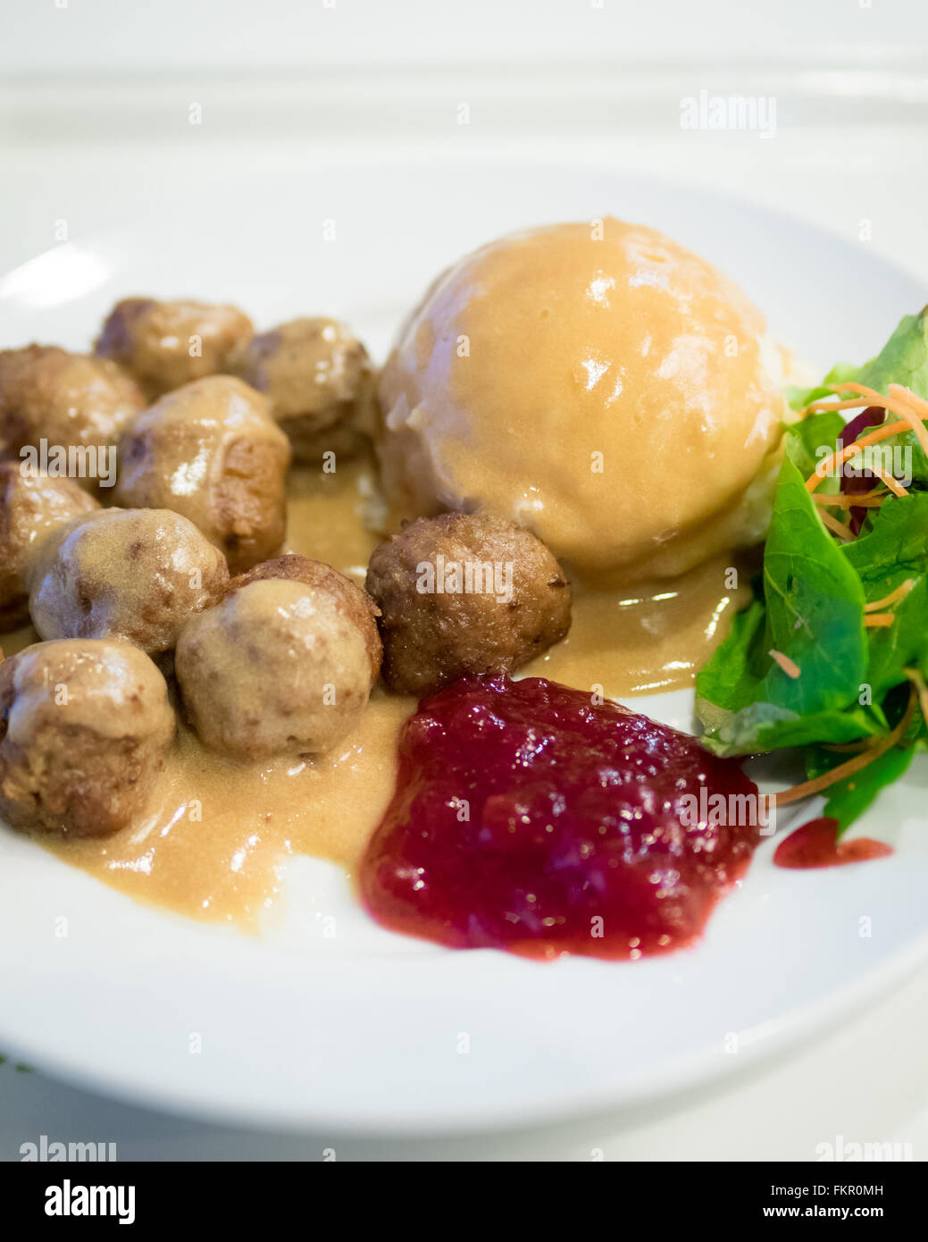 A plate of IKEA meatballs, mashed potatoes, cream gravy, green salad and lingonberry sauce. - Stock Image