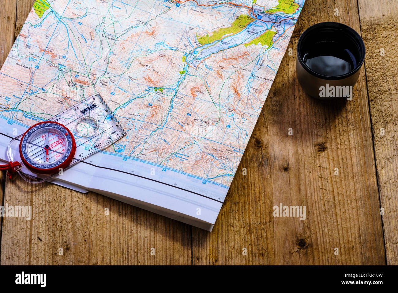 Checking route on a map with a drink. - Stock Image