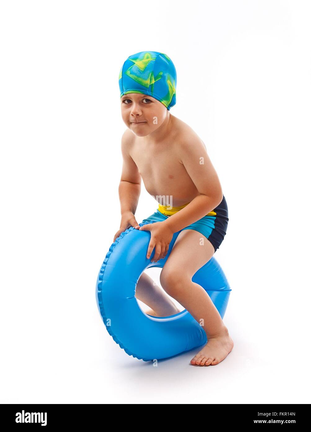 Funny little boy playing with blue life ring in swim cap, isolated in white - Stock Image