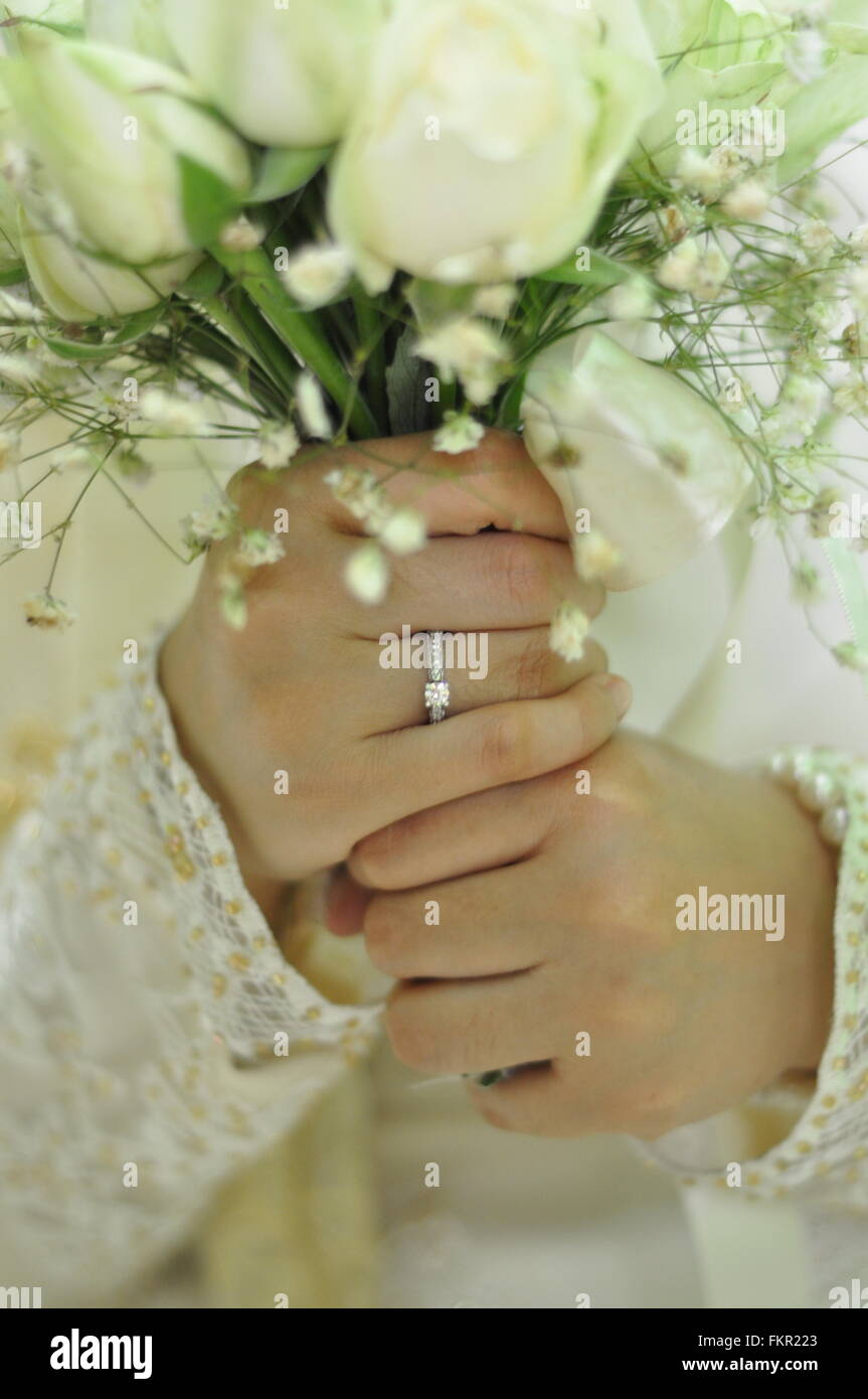 hands holding the flower bouquet in her wedding reception - Stock Image
