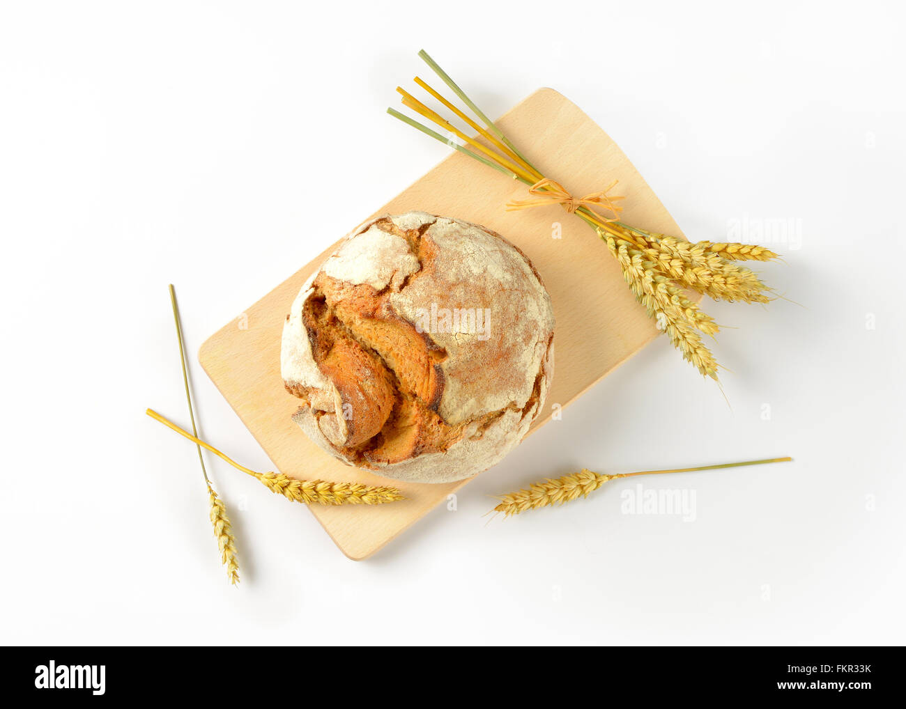 freshly baked loaf of bread and ripe ears of corn on wooden cutting board - Stock Image
