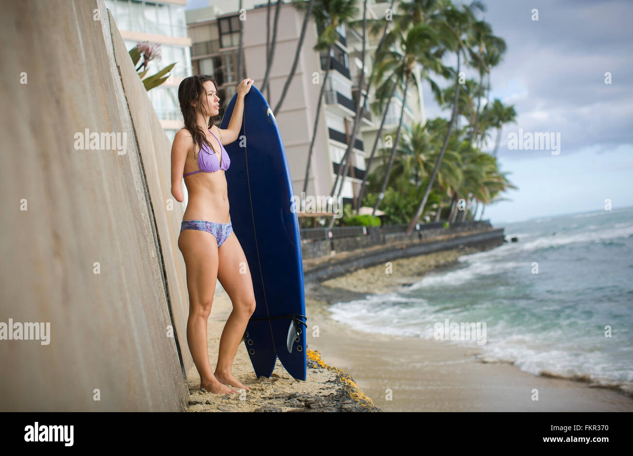 Mixed race amputee with surfboard on beach Stock Photo