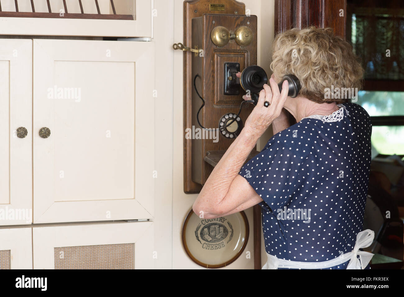 A woman in period dress talking on an old-fashioned antique wall phone - Stock Image