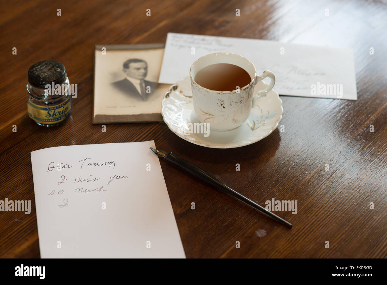 Still life from yesteryear of  a partially written letter on an old table with tea and a sepia photograph in the - Stock Image