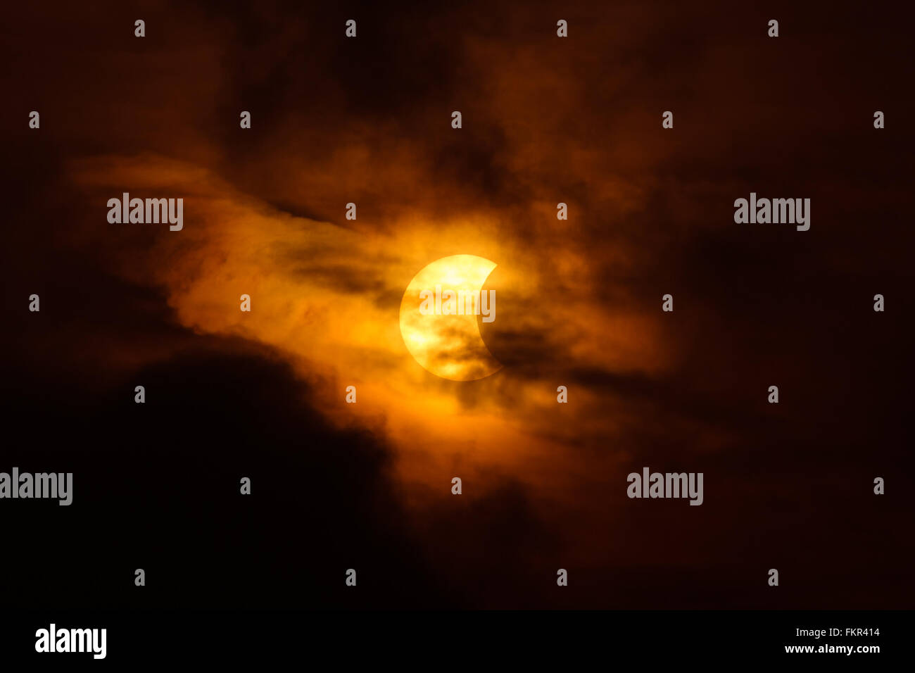 Partial solar eclipse (around 41 percent) behind dark cloud in Bangkok, Thailand on 9 March 2016. - Stock Image