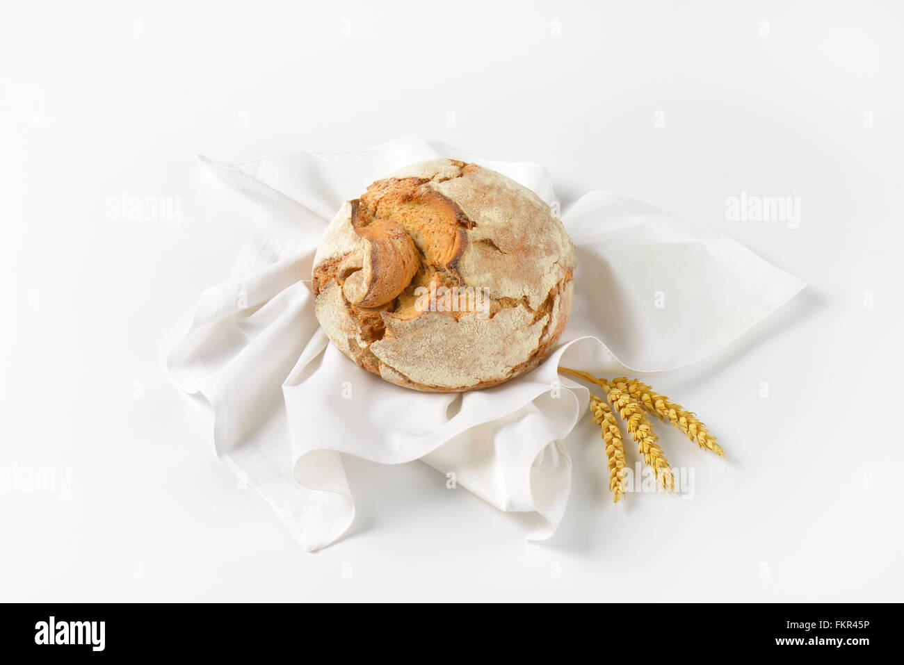 freshly baked loaf of bread and ripe ears of corn on white napkin - Stock Image