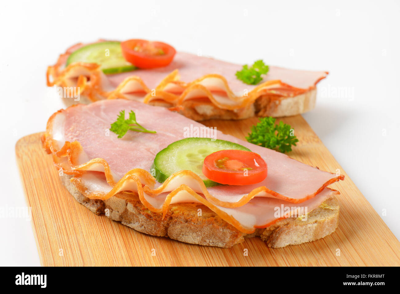 close up of two open faced ham sandwiches on wooden cutting board Stock Photo