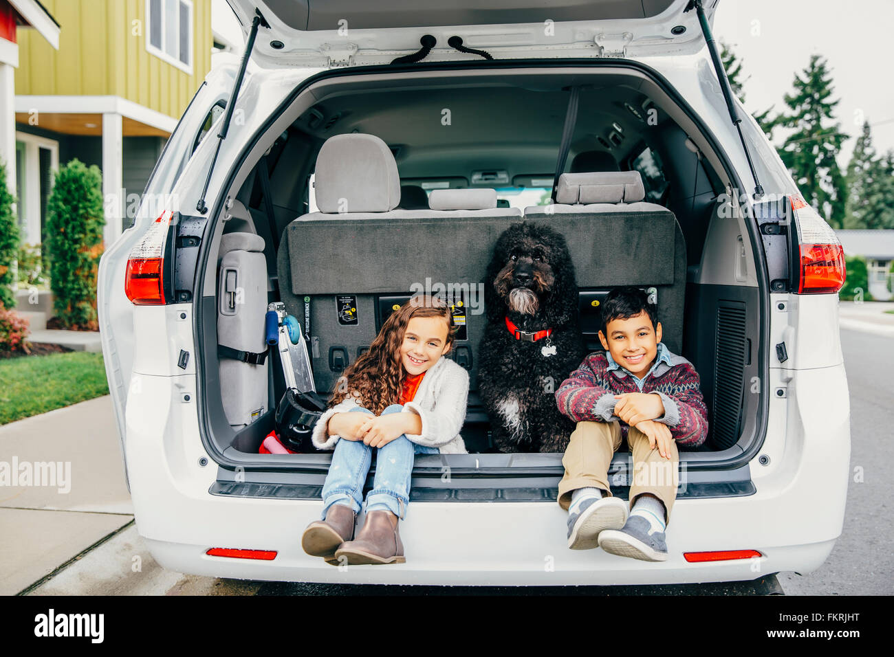 Mixed race children sitting with dog in car hatch Stock Photo