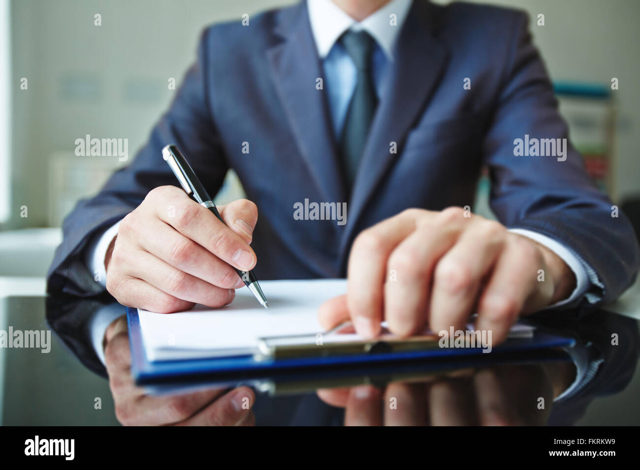 Close-up of male hand signing a document - Stock Image
