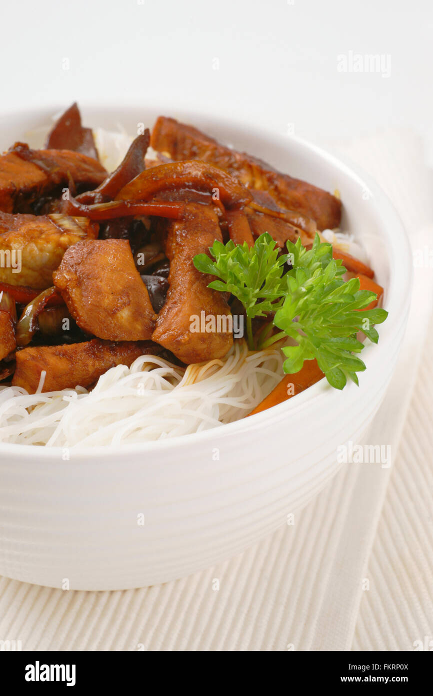 bowl of roasted meat, ear mushrooms and rice noodles on white place mat Stock Photo