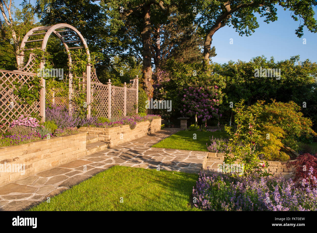 Sunlit path, flowering plants, wall, steps, trellis arch & screen - beautiful, traditional, designed, landscaped, Stock Photo