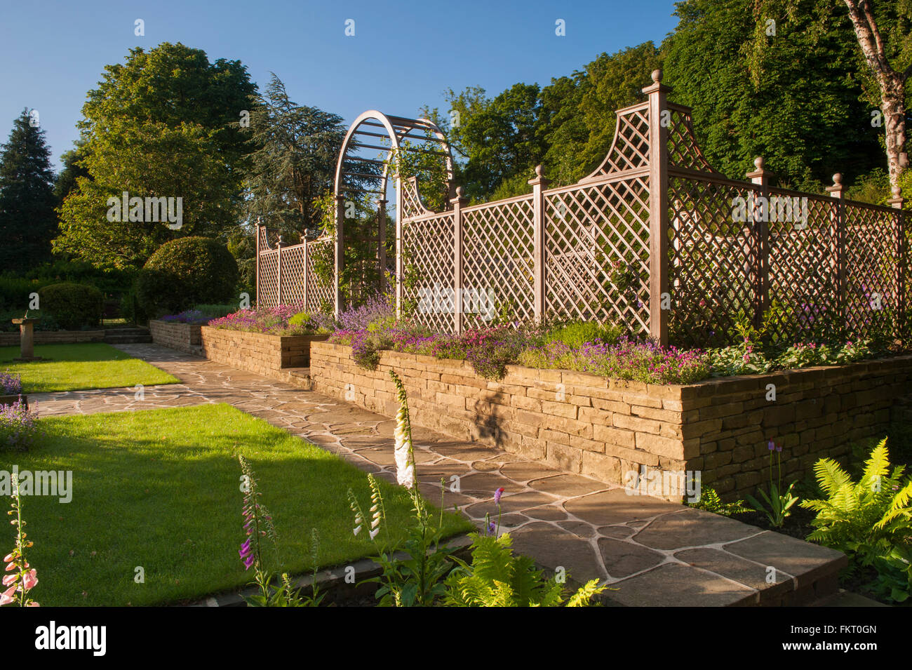 Path, flowering plants, lawn, wall, trellis arch and screen Stock ...
