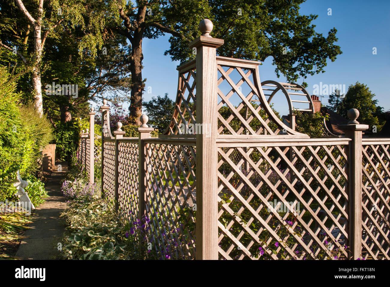 Dappled summer sun on shady path, plants, trellis fence and ...