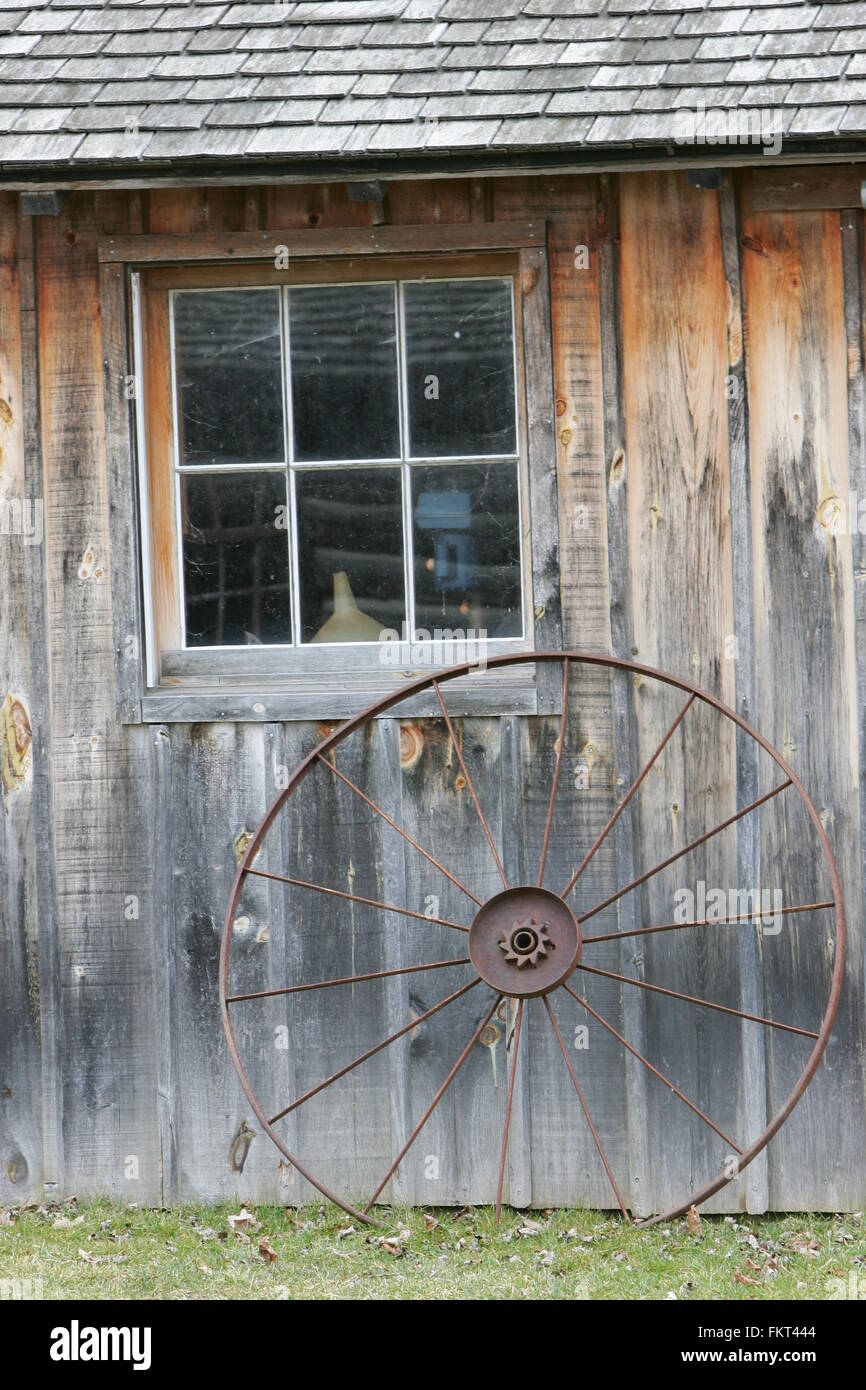 Wheel on side of the old house - Stock Image