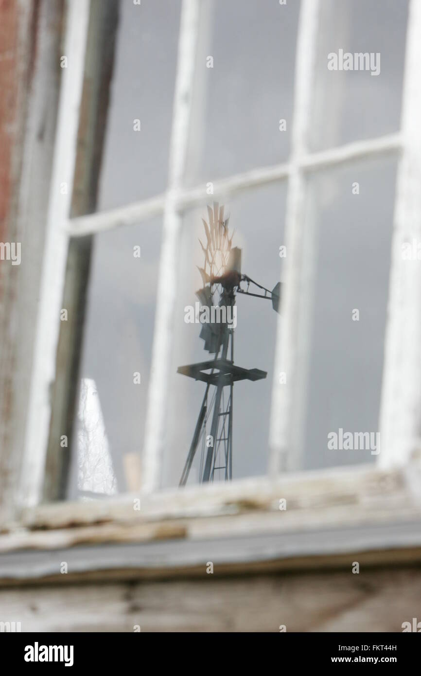 Old windmill reflection through window - Stock Image