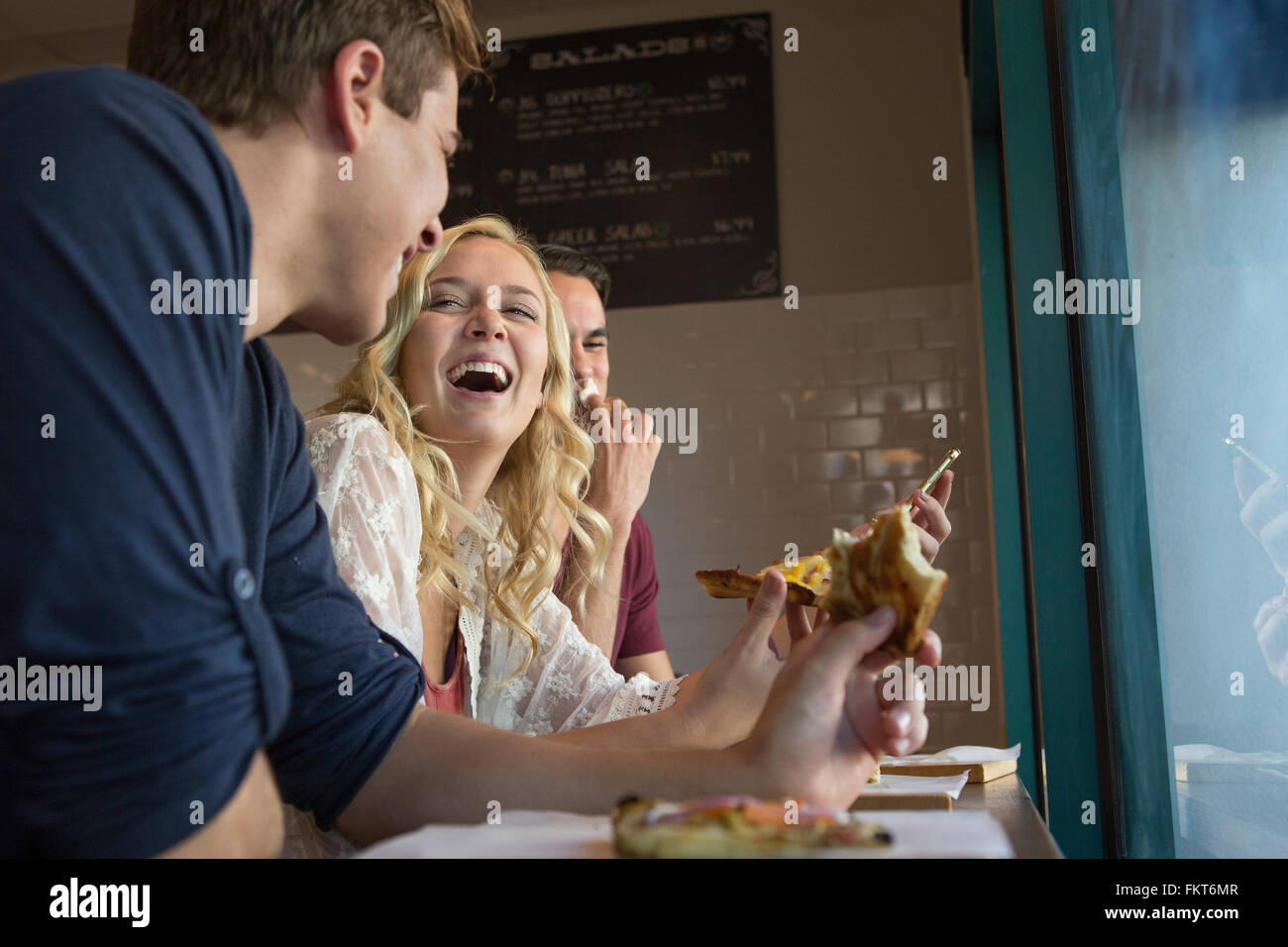 Caucasian friends eating pizza in cafe Stock Photo