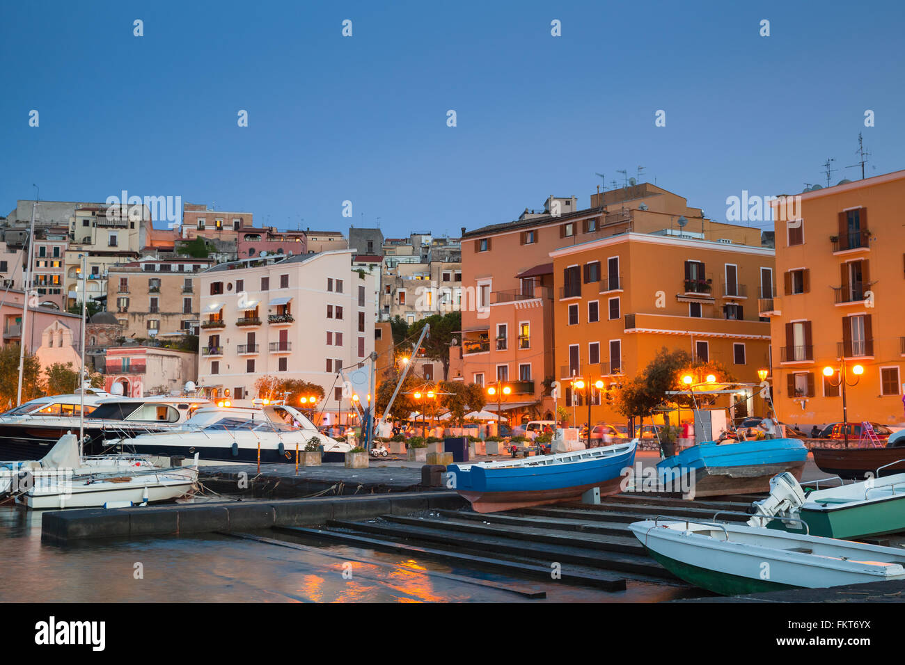 Old port with moored motorboats and yachts. Night cityscape of Gaeta town, Italy - Stock Image
