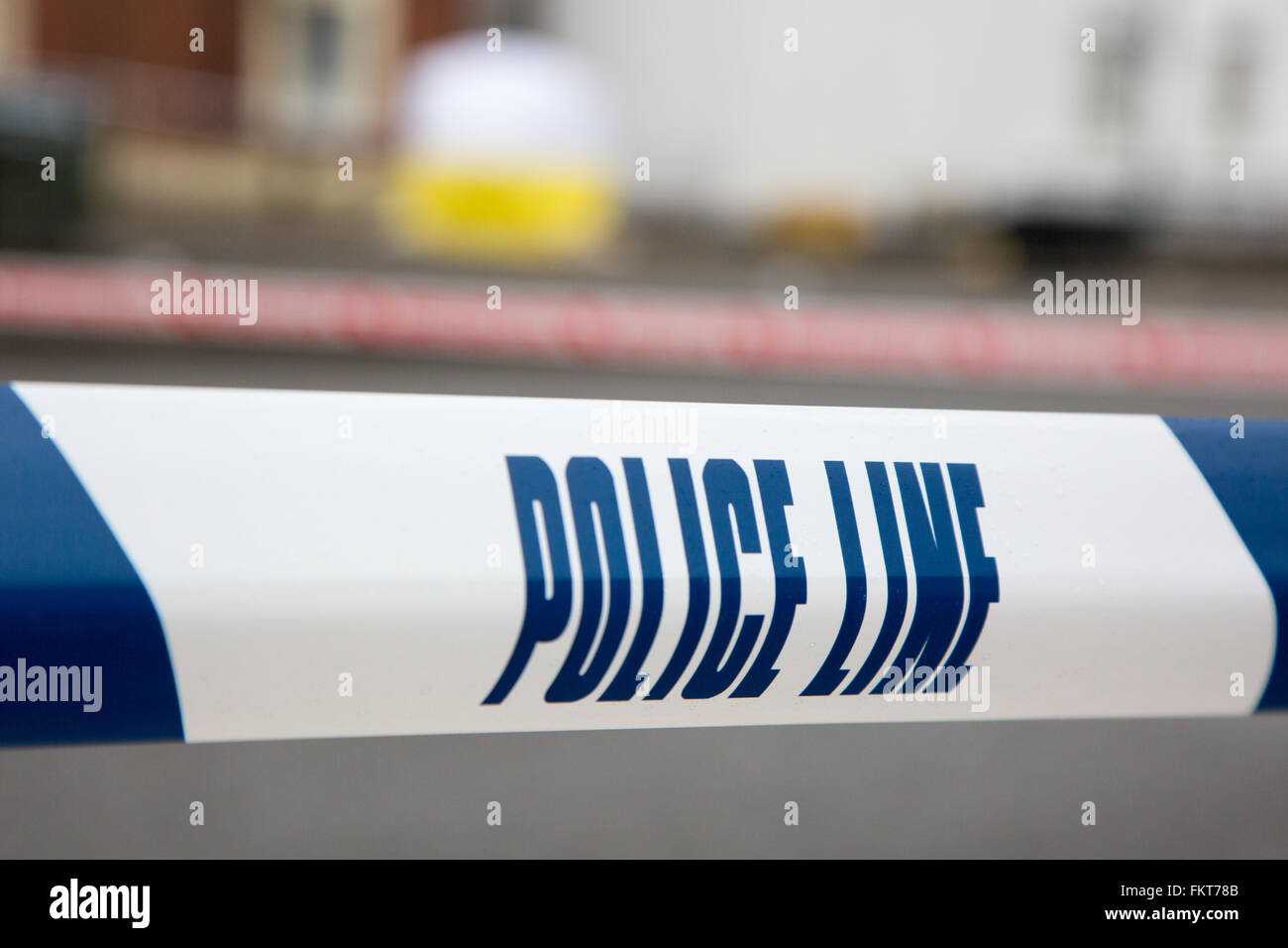 Police line around an incident in the street in front of a forensics tent - Stock Image