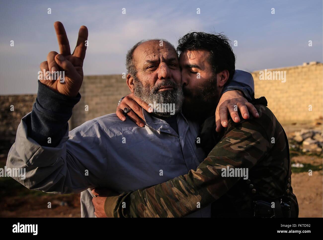 SYRIA. MARCH 10, 2016. Abu Juma (R), a commander of a Jaysh al-Thuwar unit, hugs his unidentified fellow fighterStock Photo