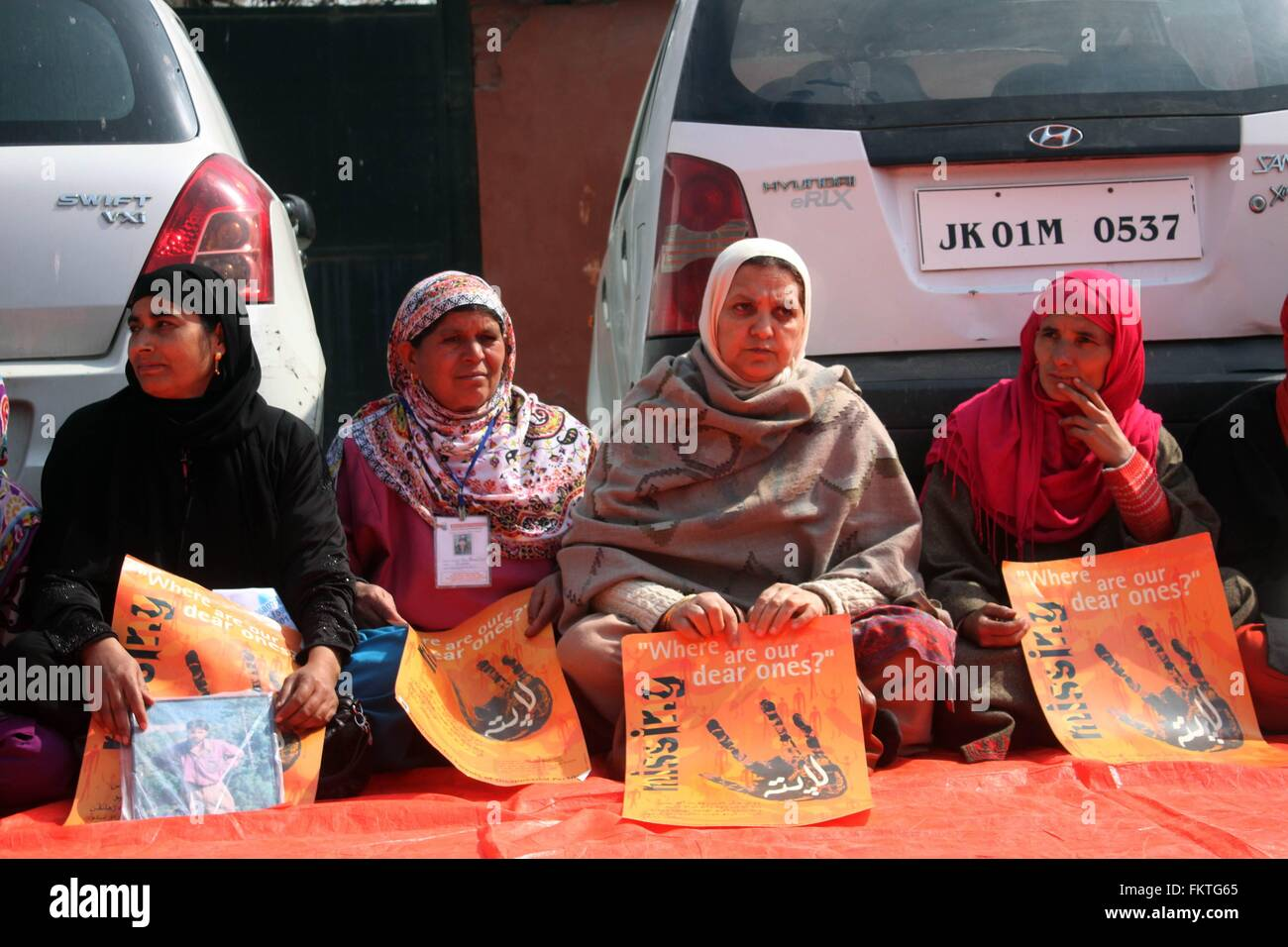 Srinagar, Kashmir. 10th Mar, 2016. Relatives of missing Kashmiri Muslims hold photographs and posters at a sit-in - Stock Image