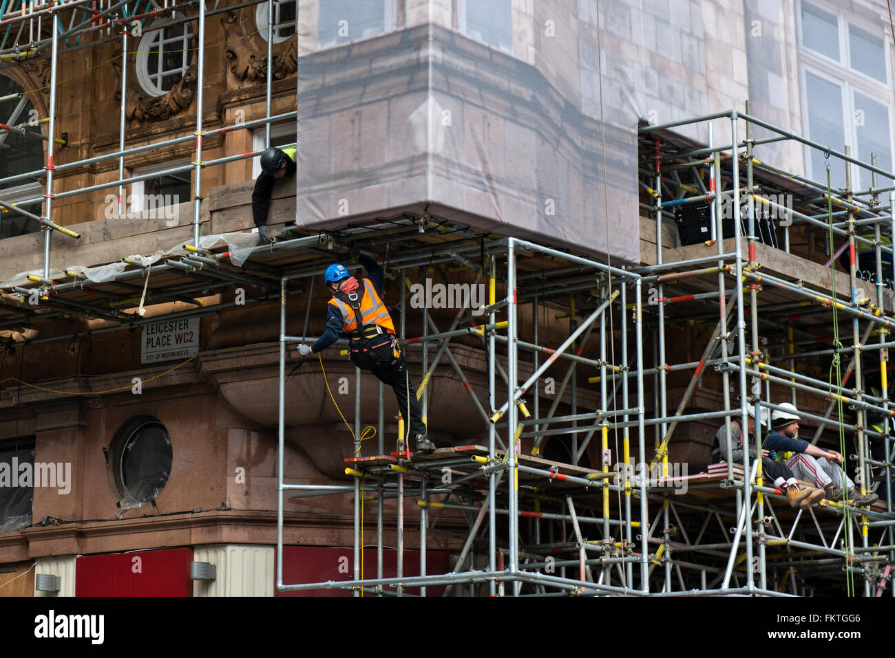 Workmen erecting scaffolding on a building in Leicester Square, West End, London, UK - Stock Image