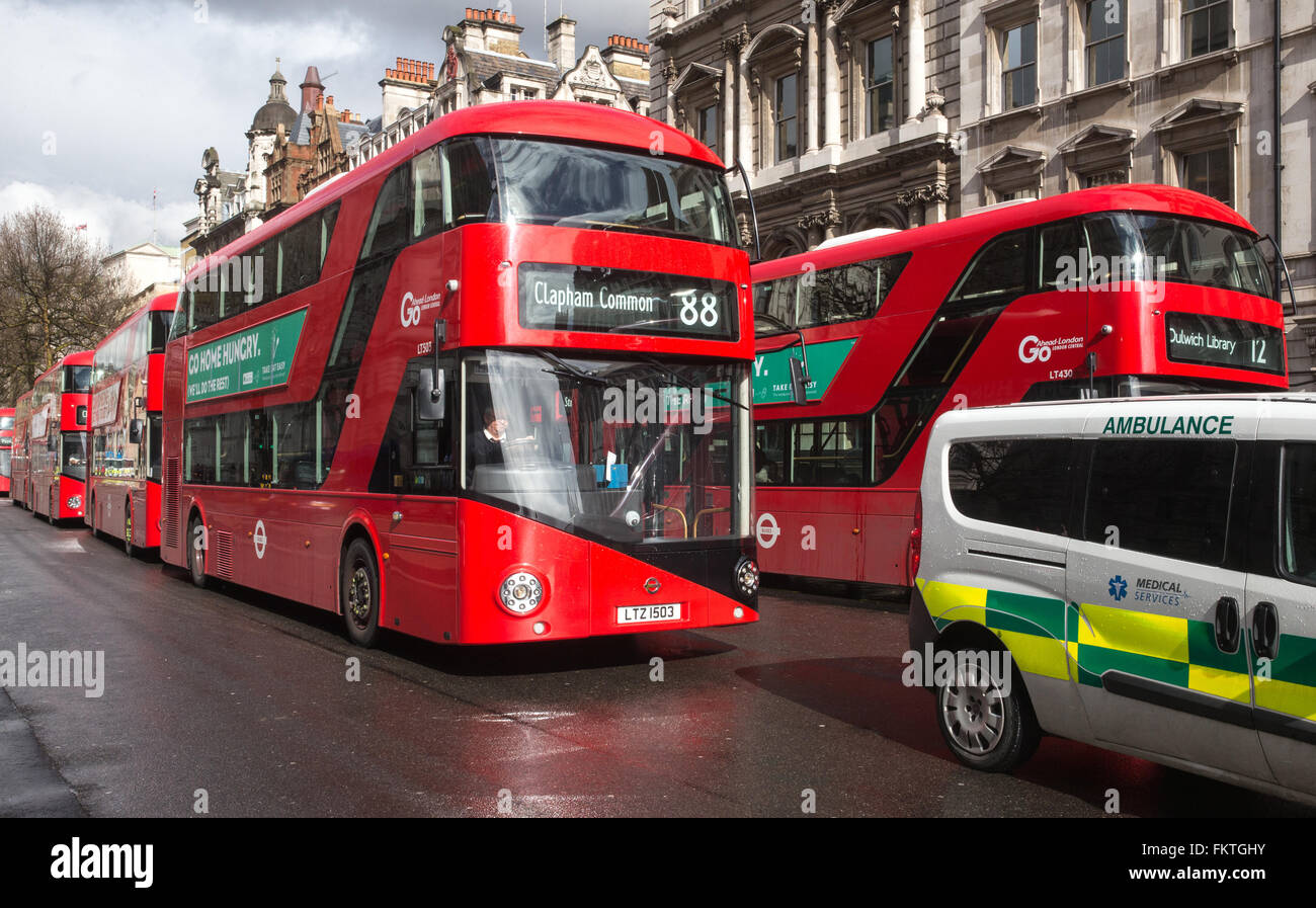 Iconic Red London buses in Whitehall near Parliament with an ambulance in the foreground - Stock Image