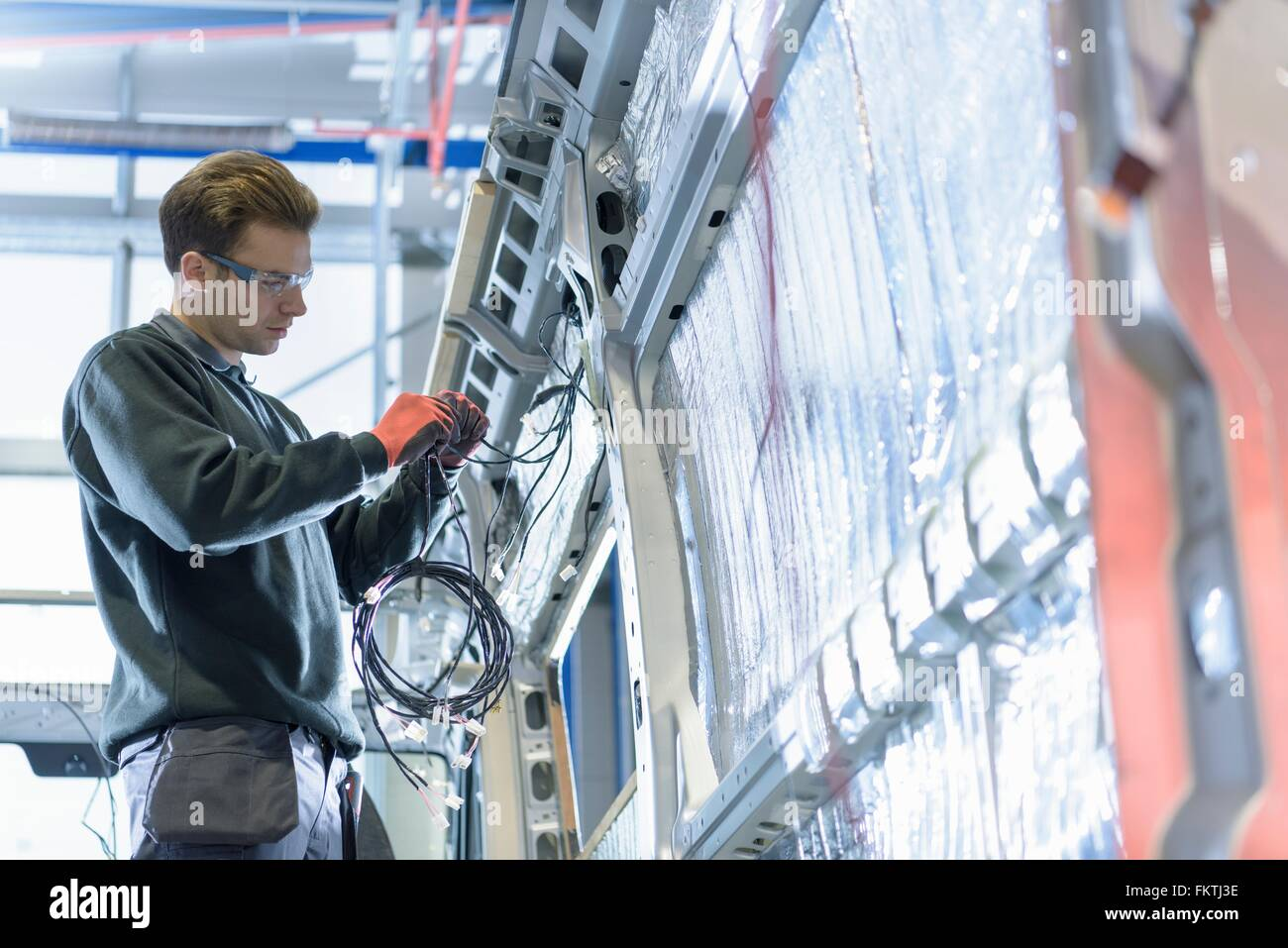 Worker fitting electrics on motorhome production line - Stock Image