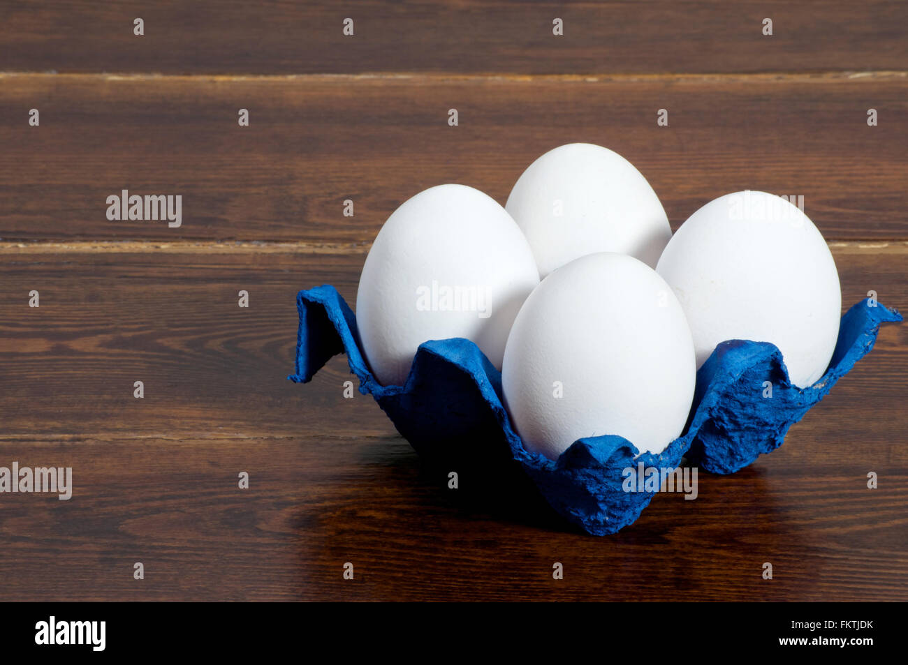 White eggs in navy blue container over wooden background side view - Stock Image