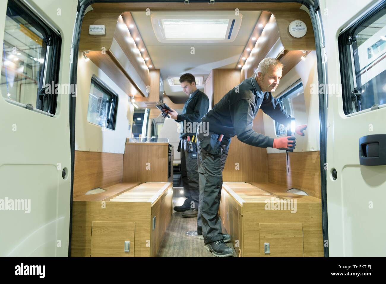 Workers inspecting vehicle on motorhome production line - Stock Image