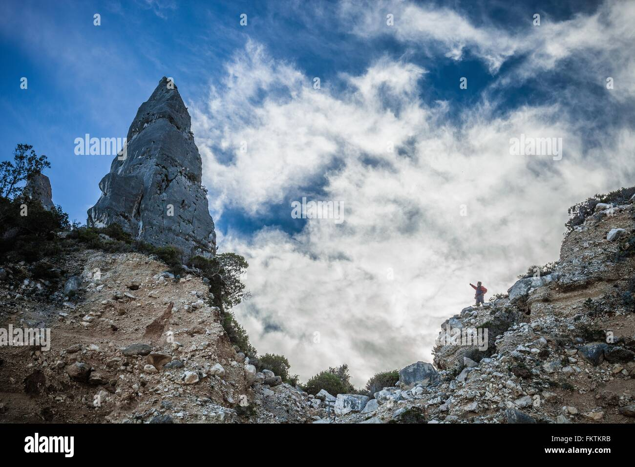 Low angle view   young man standing on cliff pointing at cone shape rock formation, Ogliastra, Sardinia, Italy - Stock Image