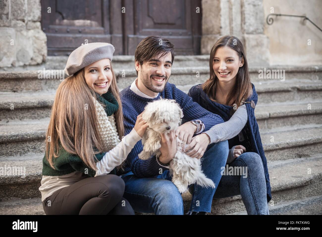 Friends sitting side by side on steps holding fluffy dog looking at camera smiling - Stock Image