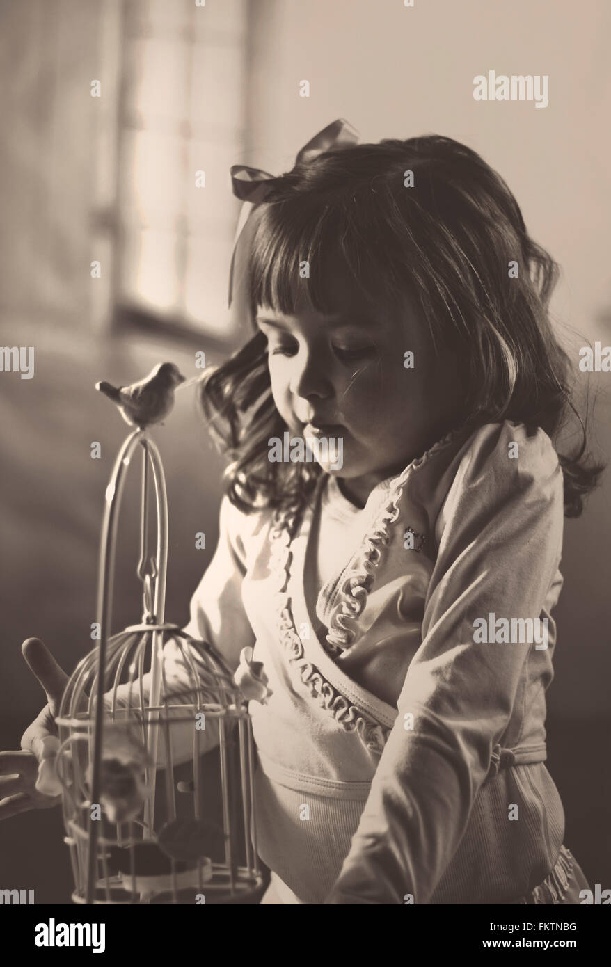 little girl playing with the bird cage - Stock Image